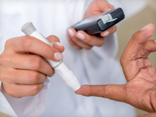 Index finger being pricked by doctor holding a glucose monitor
