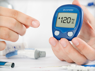 Close up of doctor holding a blue glucose monitor and pointing at it in demonstration