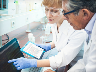 Female lab researcher shows male researcher something on a screen