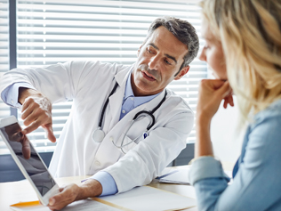 Doctor show something on a tablet to a female patient