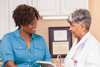 Female doctor in white lab coat consulting with patient in blue shirt